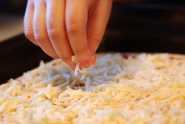 Mica adding cheese to her pizza.